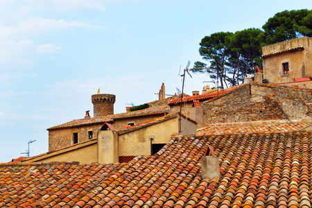 Medieval tower of the fort and the roof top of town of Tossa de Mar on the Costa Brava at the Mediterranean Sea in Spain.