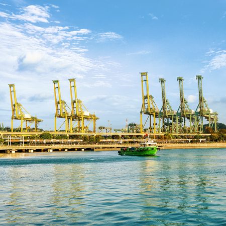 Ship and loading cranes on Sentosa Island in Singapore. Port Container terminal on the background Stock Photo