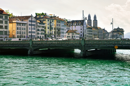 Bridge at Limmatquai and Grossmunster Church in Zurich, Switzerland. People on the background