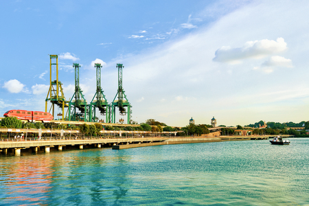 Passenger Express Train and loading cranes of Sentosa Island, in Singapore. Port Container terminal on the background
