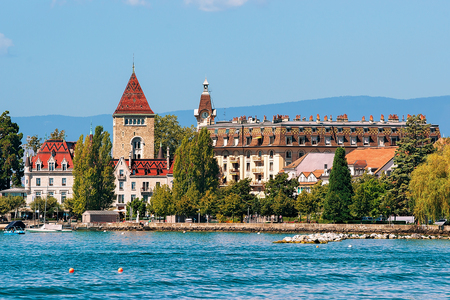 Chateau Ouchy at Lake Geneva quay in Lausanne, Switzerland. People on the background Archivio Fotografico