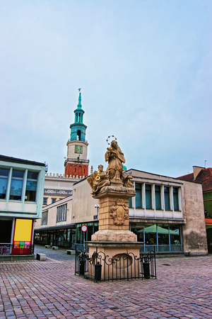 Poznan, Poland - May 6, 2014: Statue of St John Nepomuk holding cross on Old Market Square in the city center of Poznan, Poland. Spire of Old Town Hall on the background