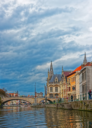 Old city center Graslei with St Michael Bridge over Leie River and Former Post Office in Ghent in East Flanders, Belgium. People on the background