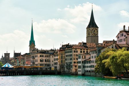 Limmat River quay and Saint Peter Church and Fraumunster Church in the city center of Zurich, Switzerland.