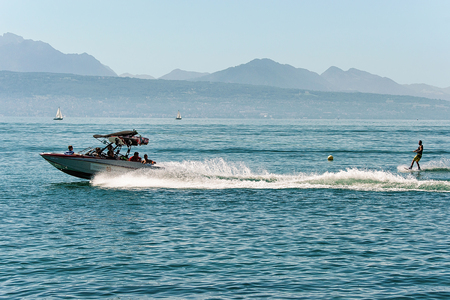 Lausanne, Switzerland - August 26, 2016: Motor boat with man wakeboarding in Lake Geneva in Lausanne, Switzerland Stock Photo