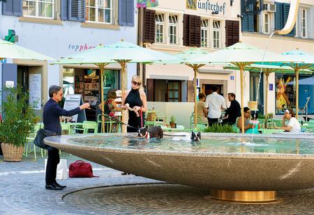 september 2: Zurich, Switzerland - September 2, 2016: People bathing dogs in the fountain at Munsterhof square in Zurich, Switzerland