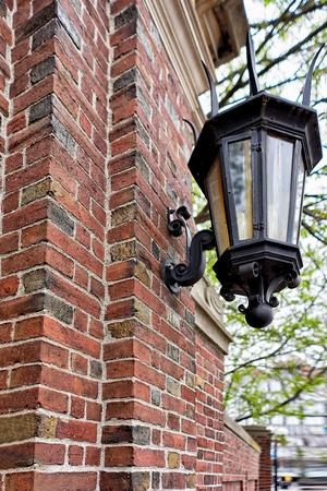 prestigious: Cambridge, USA - April 29, 2015: Street lantern of Harvard University Building Wall at Harvard Yard in Cambridge, Massachusetts, MA, USA. It is one of the prestigious learning institutions in the world.