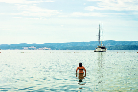 seafronts: Omis, Croatia - August 18, 2016: Woman in the Adriatic sea in Omis, Croatia Stock Photo