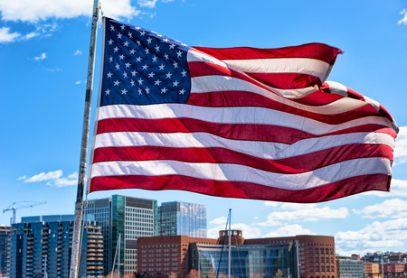 Beautiful city waterfront and skyline and American flag in Boston, MA, United States. Standard-Bild