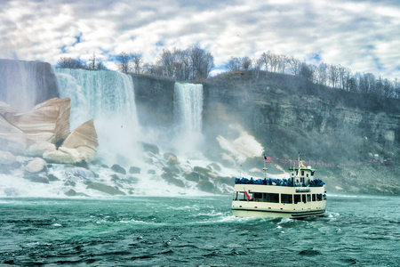 the edge of horseshoe falls: Niagara Falls and ship. A view from Niagara State Park on American Falls, Bridal Veil Falls, Goat Island and Horseshoe falls on the background. Stock Photo