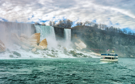 Niagara Falls and ferry. A view from Niagara State Park on American Falls, Bridal Veil Falls, Goat Island and Horseshoe falls on the background. Stock Photo