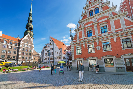 Riga, Latvia - September 3, 2014: Square with people and House of Blackheads and St Peter Church in the historical center in the old town of Riga, Latvia.