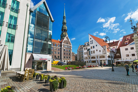 Riga, Latvia - September 3, 2014: Square with people and spire of Saint Peter Church in the historical center in the old town of Riga, Latvia. Editorial