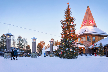 rovaniemi: Rovaniemi, Finland - March 5, 2017: People in Santa Claus Office in Santa Village with Christmas trees, Lapland, Finland, on Arctic Circle in winter.