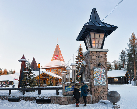 rovaniemi: Rovaniemi, Finland - March 5, 2017: Couple in Santa Claus Office in Santa Village with Christmas trees, Lapland, Finland, on Arctic Circle in winter. People on the background