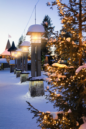 Street lantern in Santa Claus Village with Christmas trees at dusk, Lapland, Finland, on Arctic Circle in winter.