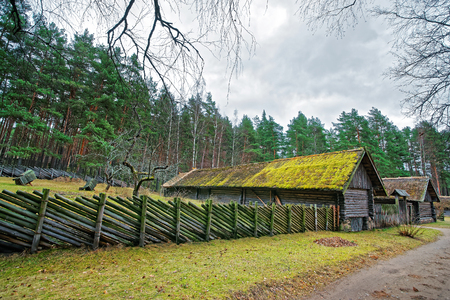 ethnographical: Old building and wooden fence in Ethnographic open air village in Riga, Latvia Editorial