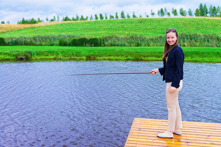 Young girl fishing at the countryside, Vilnius, Lithuania.