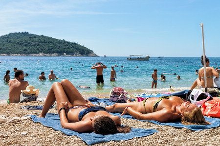 seafronts: Dubrovnik, Croatia - August 20, 2016: Women sunbathe in beach at Adriatic Sea in Dubrovnik, Croatia