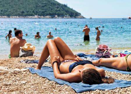 Dubrovnik, Croatia - August 20, 2016: Woman sunbathing on beach in Adriatic Sea in Dubrovnik, Croatia