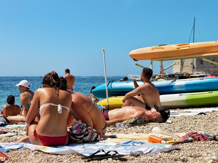 Women sunbathing on the beach at Dalmatian Coast of Adriatic Sea in Dubrovnik, Croatia Stock Photo