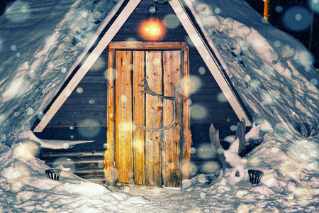 rovaniemi: Lappish traditional house at the reindeer farm in winter Rovaniemi, Lapland, Finland. Night snowfall. Toned