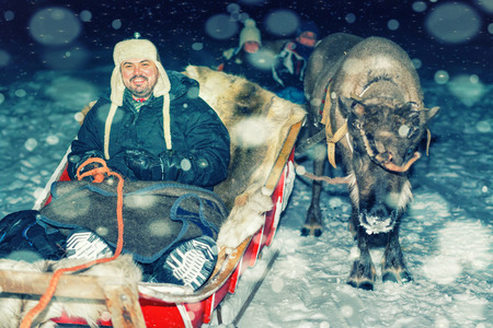 Man on reindeer sledge at night safari in the winter forest in Rovaniemi, Lapland, Finland. Snowfall. Toned