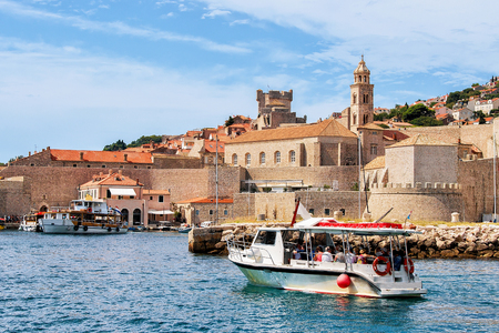 ragusa: Dubrovnik, Croatia - August 19, 2016: Motor boat with people at the Old port in the Adriatic Sea of Dubrovnik, Croatia. Dominican Monastery steeple on the background