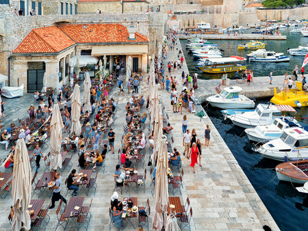 Dubrovnik, Croatia - August 19, 2016: People at the cafe in the Old port of Dubrovnik, in Croatia.