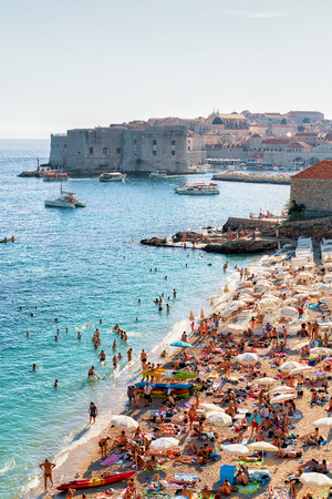 Dubrovnik, Croatia - August 18, 2016: Beach full of people and Dubrovnik fortress in the Adriatic Sea, Croatia