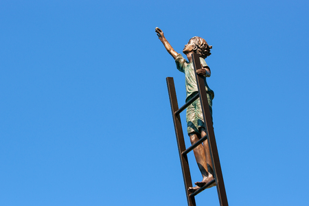 montreux: Montreux, Switzerland - August 27, 2016: Sculpture with a boy on the ladder at Geneva Lake embankment in Montreux, Vaud canton, Switzerland Stock Photo