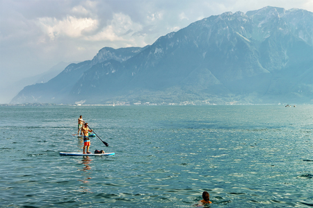Vevey, Switzerland - August 27, 2016: People standing on Standup paddle surfing board on Geneva Lake in Vevey, Vaud canton, Switzerland