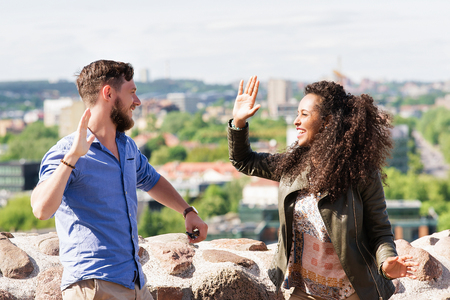Young smiling multiracial couple clap their hands as diversity friendship and togetherness concept