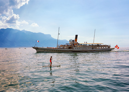 vevey: Vevey, Switzerland - August 27, 2016: Woman on standup paddle board and excursion ship at Geneva Lake of Vevey, Swiss Riviera. Alps mountains on the background