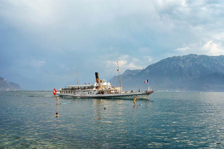 Vevey, Switzerland - August 27, 2016: People on standup paddle board surfing and excursion ferry at Geneva Lake of Vevey, Swiss Riviera. Alps mountains on the background Editorial
