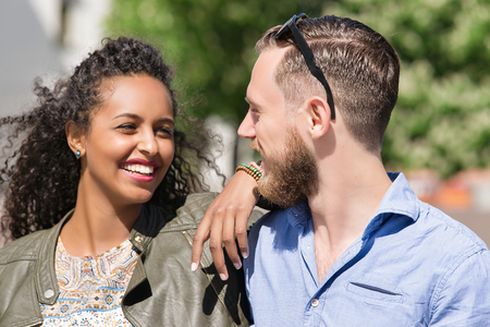 tenderly: Young multiracial couple looking at each other tenderly while dating as diversity friendship and togetherness concept Stock Photo