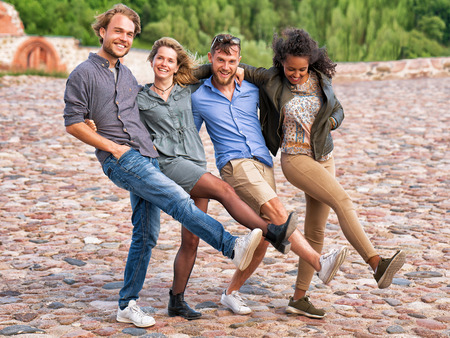 Group of smiling young friends trying to raise and move their legs simultaneously as fun togetherness activity concept