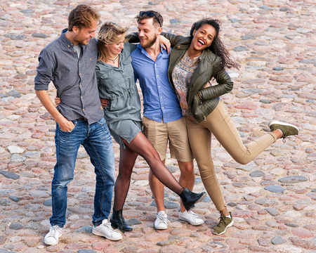 Group of smiling young friends trying to raise and move their legs simultaneously as a fun togetherness activity Concept Stock Photo