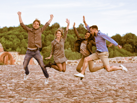 Group of smiling young multiracial friends trying to jump up simultaneously as fun togetherness activity concept