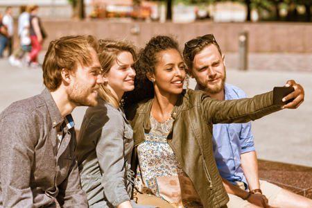 Young middle eastern girl making selfie with her friends via the mobile phone Concept