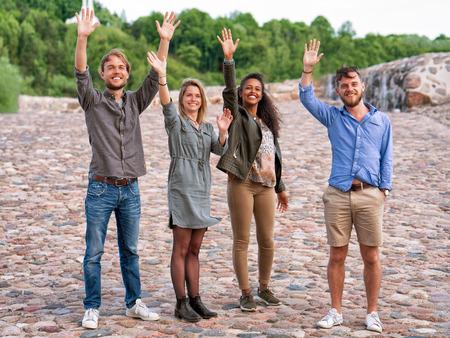 Groep jonge vrienden die hun handen golven als gebaar van groetconcept