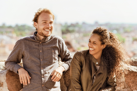 Smiling young mixed race girl with caucasian friend standing and relaxing together as diversity friendship and togetherness concept Archivio Fotografico