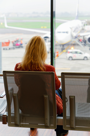 milánó: Woman sitting and waiting for her flight in the departure hall of Milan-Bergamo airport, Italy. Airplane on the background
