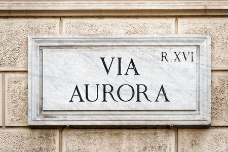 ローマ、イタリアの壁にオーロラ路上標識を介して 写真素材