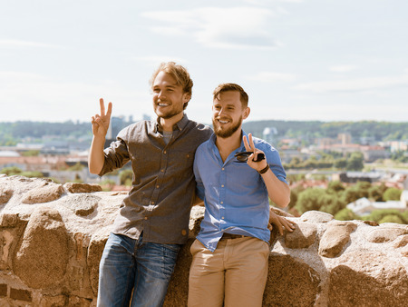 Smiling young caucasian buddies in front of city skyline as travel and friendship concept
