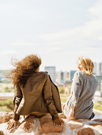 Two female friends enjoy the city skyline view concept
