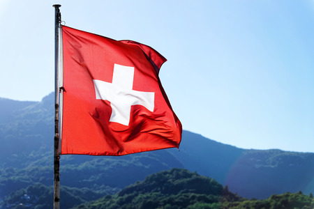 Flag of Switzerland waving in the wind. Swiss Alps on the background