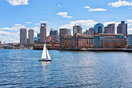 Sailboat traveling across Charles river with the skyline of the city in the background in Boston, America