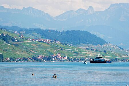 Lausanne, Switzerland - August 26, 2016: People swimming and water ferry on Lake Geneva at Ouchy embankment in Lausanne, Switzerland. People aboard Editorial