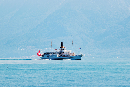 Water ferry ship with Swiss flag in Lake Geneva at Ouchy embankment, Lausanne, Switzerland. People aboard